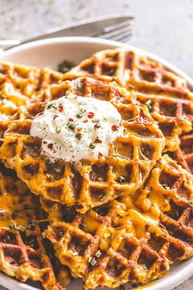 Cheesy Potato Waffles - Delicious, cheesy, and savory waffles prepared with leftover mashed potatoes and cheddar cheese.Crispy on the outside and fluffy on the inside, these potato waffles not only taste amazing, but they are a super fun meal to serve to your family.