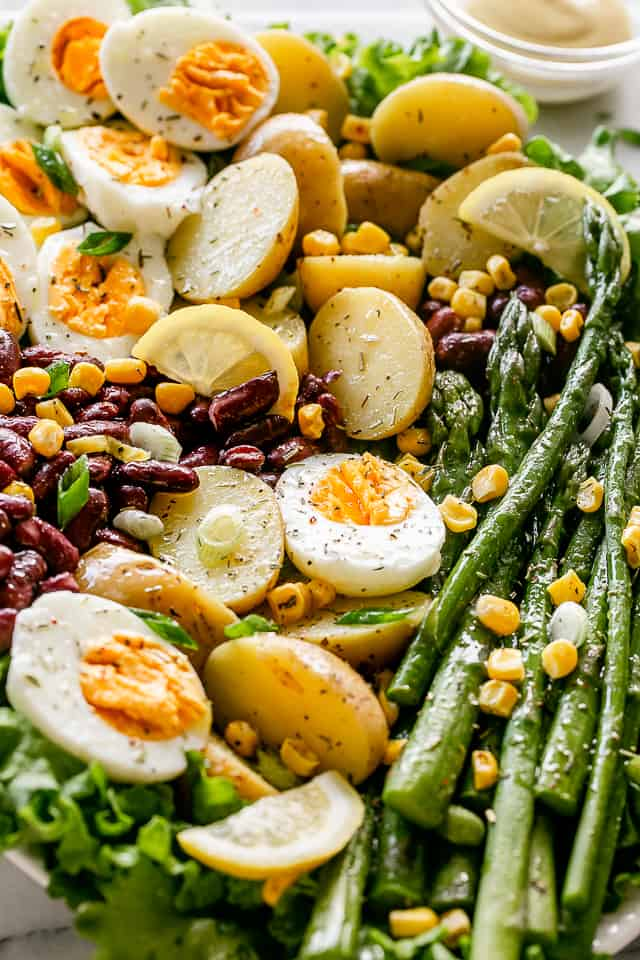 Hard boiled eggs and asparagus over fresh lettuce.