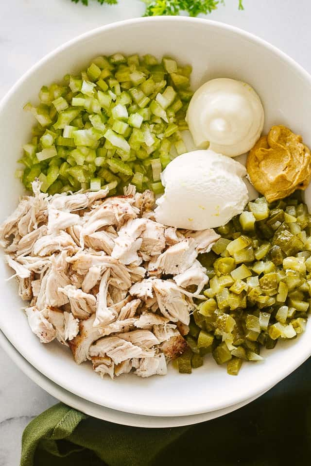 Dill pickles, shredded chicken, celery, and mayo dressing inside a salad bowl.
