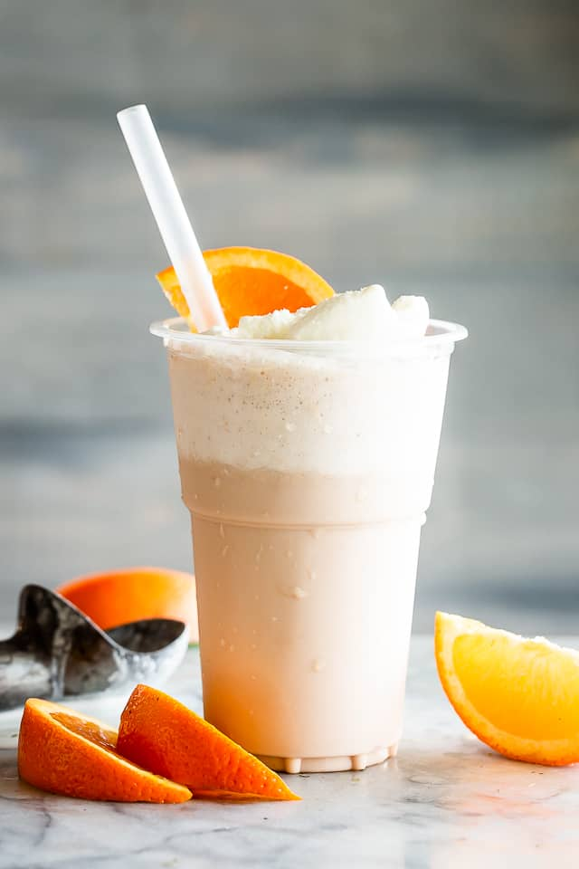 Creamsicle Ice Cream Float in a cup with orange slices and a straw.
