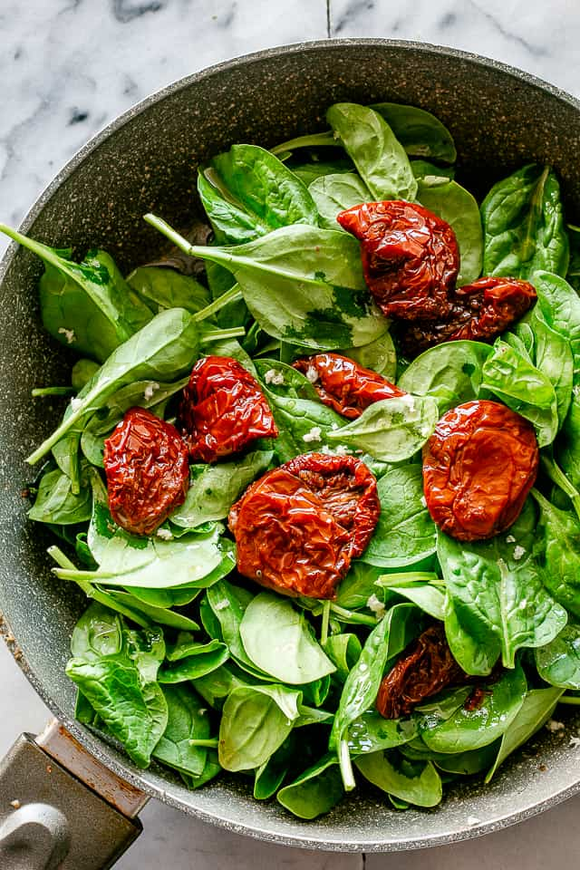 Baby spinach and sun-dried tomatoes in a skillet.