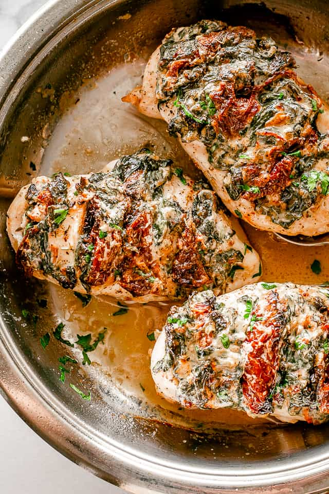 Baked chicken breasts in a skillet.