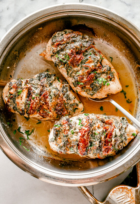 Hasselback chicken breasts in a skillet.