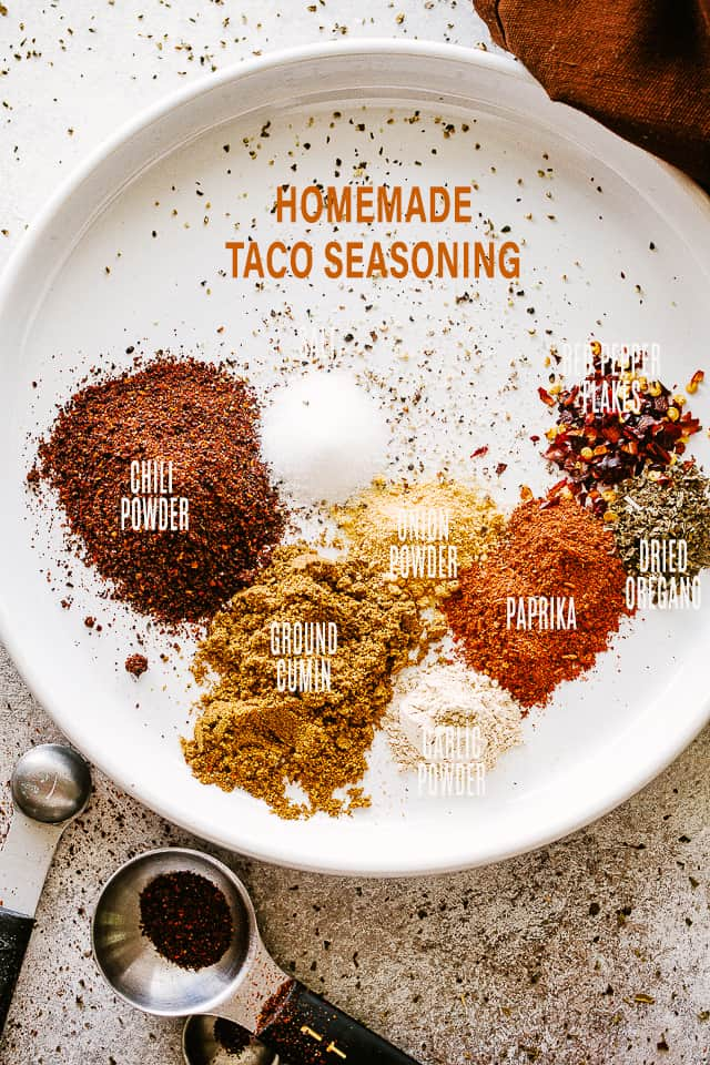 Spices and seasonings for tacos set on a white plate.