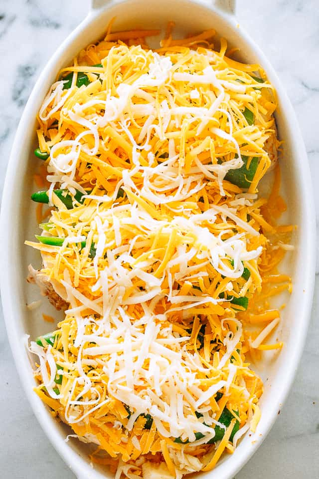 Chicken breasts in a baking dish topped with jalapenos and cheese.
