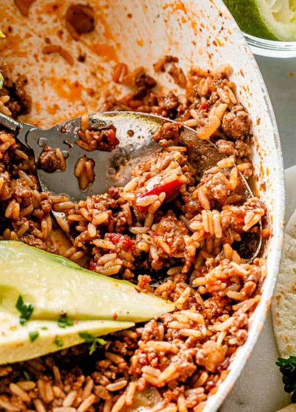 Scooping out ground beef and rice from a skillet.
