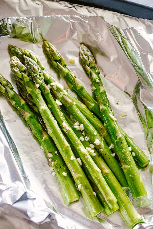 Fresh asparagus stalks on foil.