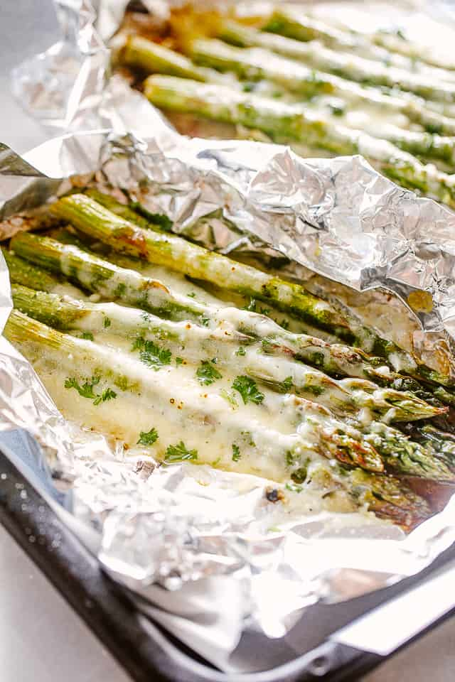 Asparagus topped with cheese in foil packets.