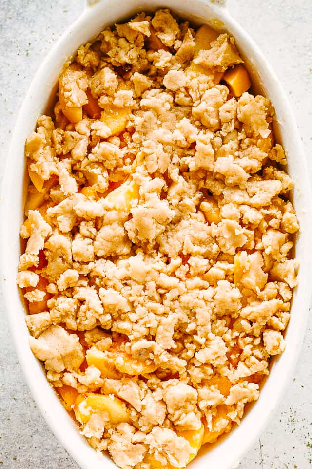 Unbaked peach cobbler with raw topping.