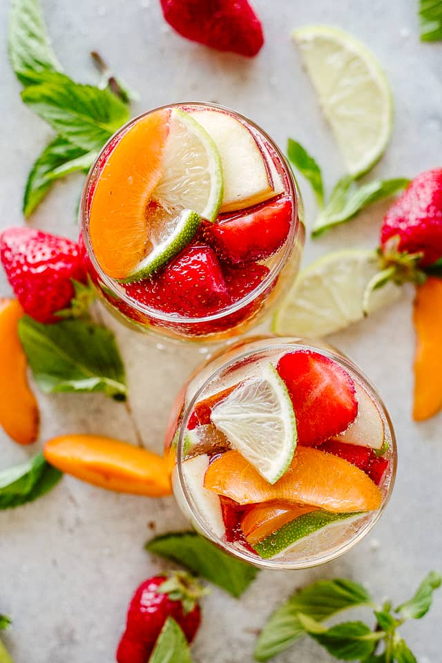2 glasses filled with White Wine Sangria and fruits.