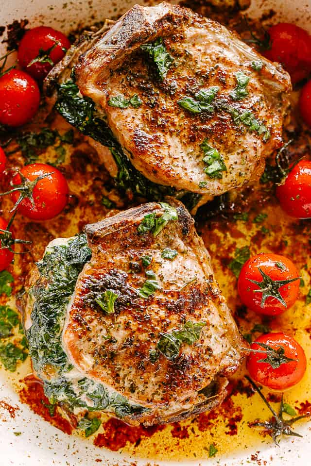 Spinach and blue cheese stuffed pork chops in a skillet with cherry tomatoes.