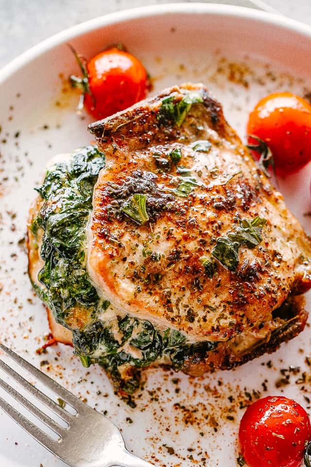Spinach stuffed pork chops on a white plate with a fork.