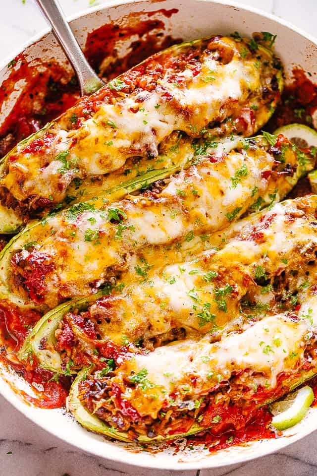 Taco meat stuffed zucchini in a baking dish.