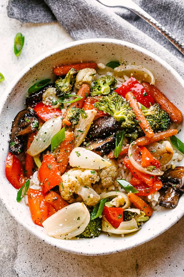 Roasted vegetables served over a bowl of rice.