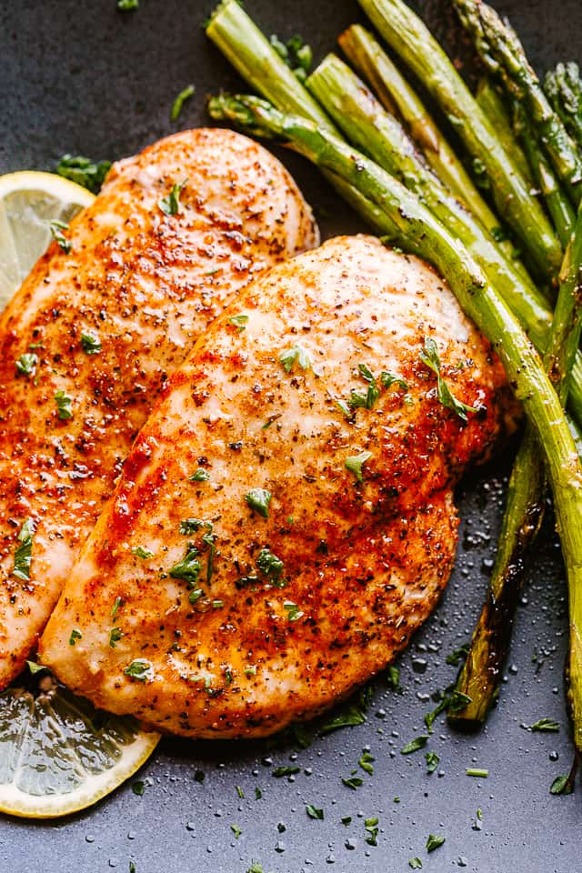 Air Fryer Chicken served on a black plate with asparagus.