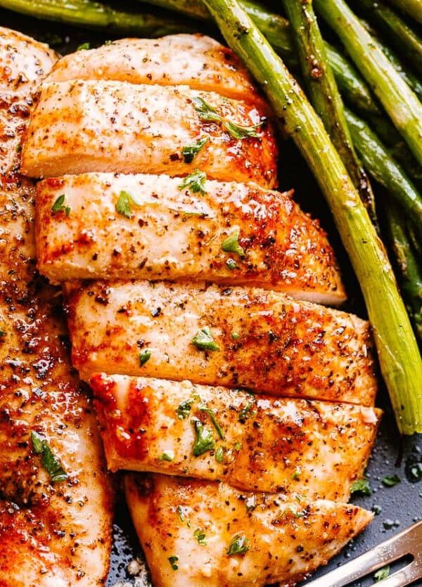 Air Fryer prepared chicken breasts served with asparagus.