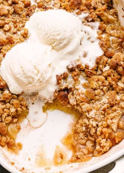 Baked Apple Crumble topped with two scoops vanilla ice cream.