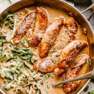 Chicken tenders cooked in a skillet with cream sauce and zoodles.