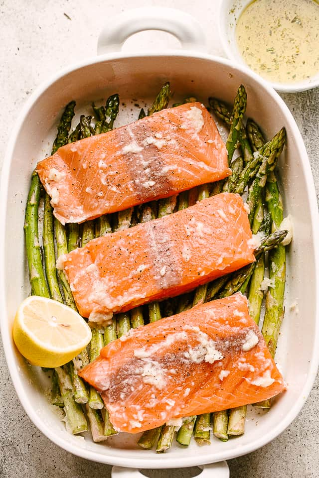 Baking dish with raw salmon fillets set on top of fresh asparagus.