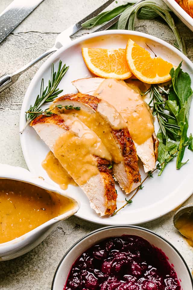 Plated slices of turkey breast with gravy.