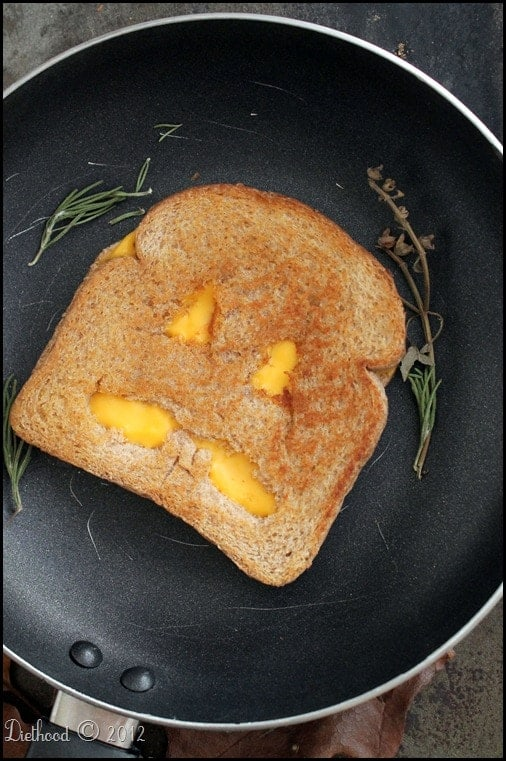 Jack o' lantern faced grilled cheese sandwich in a skillet.