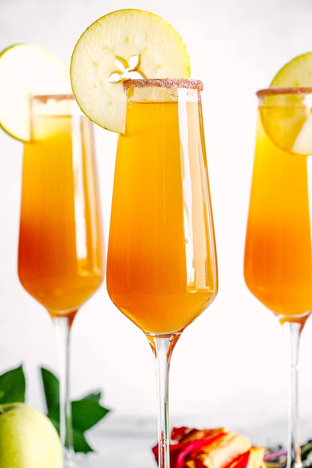 Apple Cider Mimosa in champagne flutes with apple slices.
