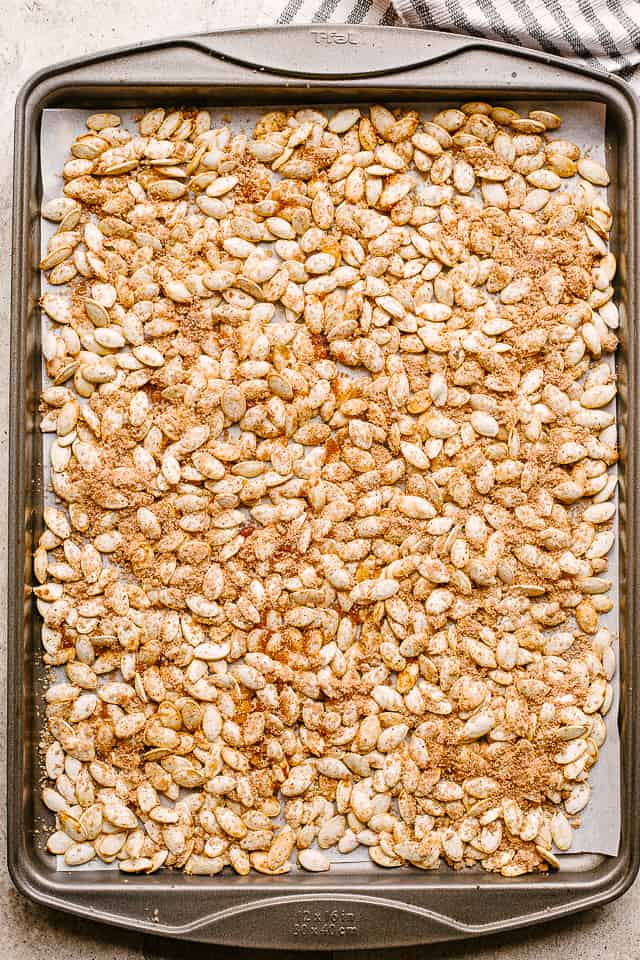 raw pumpkin seeds on a baking sheet