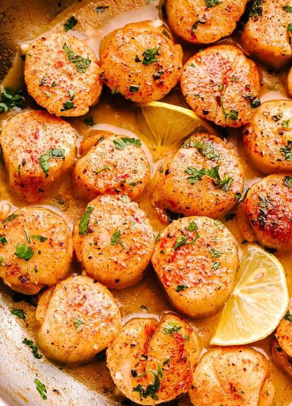 scallops in butter sauce with parsley and lemon slices