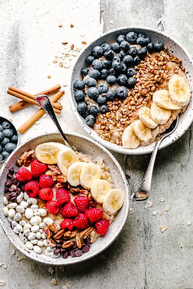 two bowls of oatmeal with fruit toppings