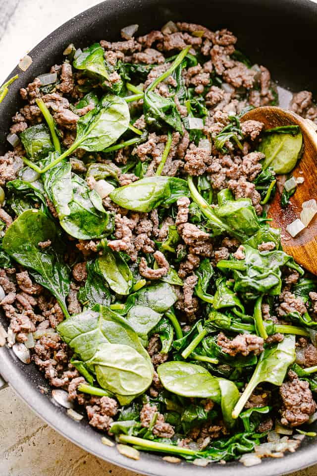 Ground beef and spinach sauteing in a pan