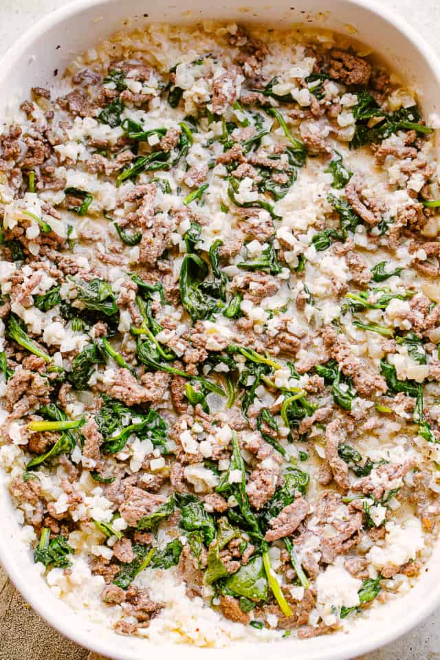 Spinach and ground beef sauteing in a pan