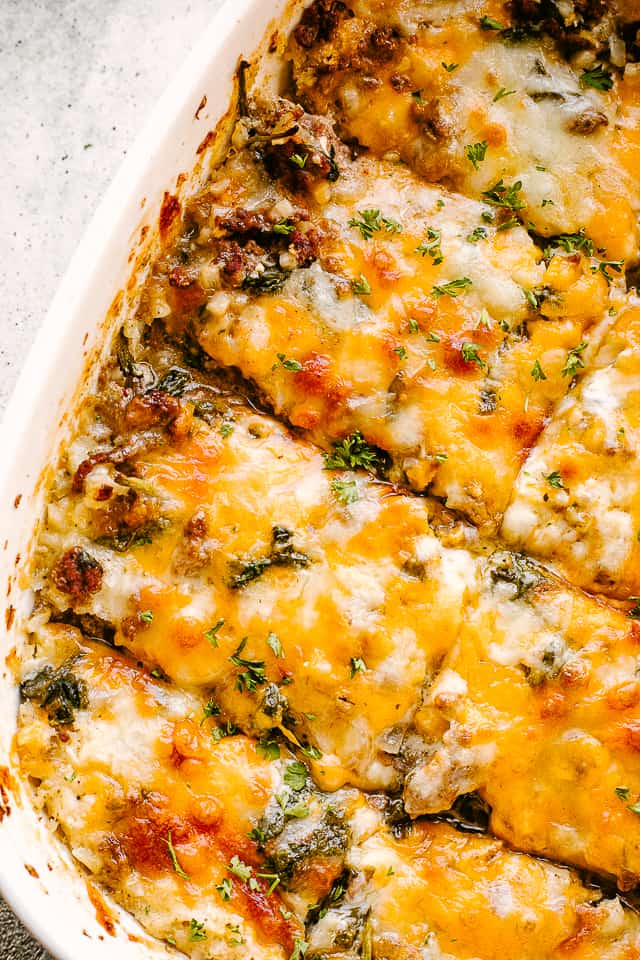 Ground beef cauliflower casserole sliced with melted cheese over the top