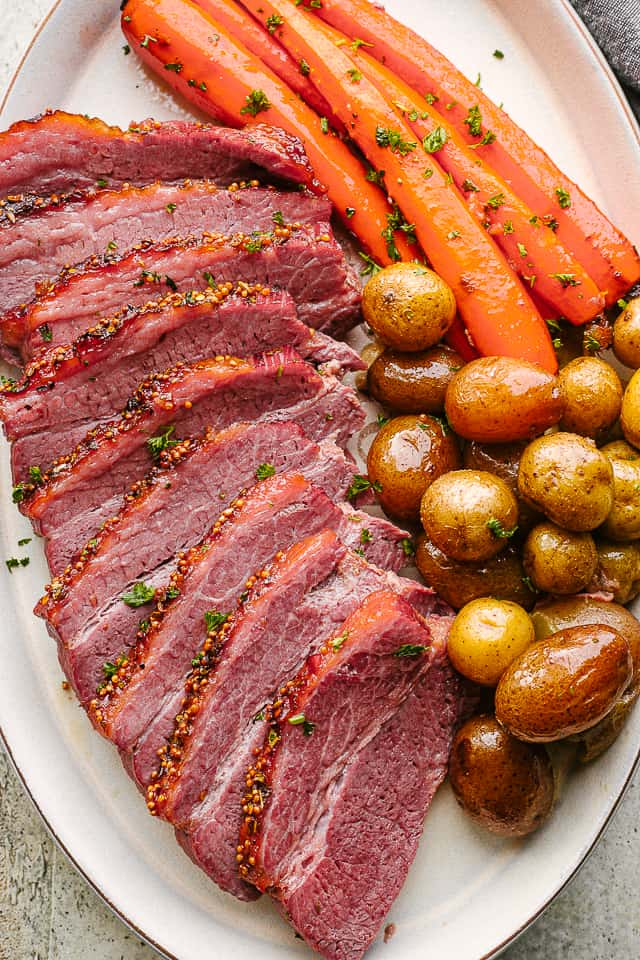 Crock Pot corned beef sliced and served with potatoes and carrots