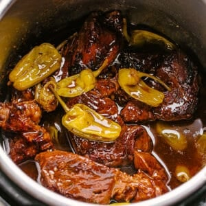 A pot roast cooking in an Instant Pot with pepperoncini