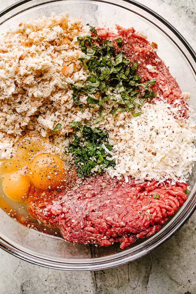 Meat, bread crumbs. eggs, and herbs ready to be combined into meatballs