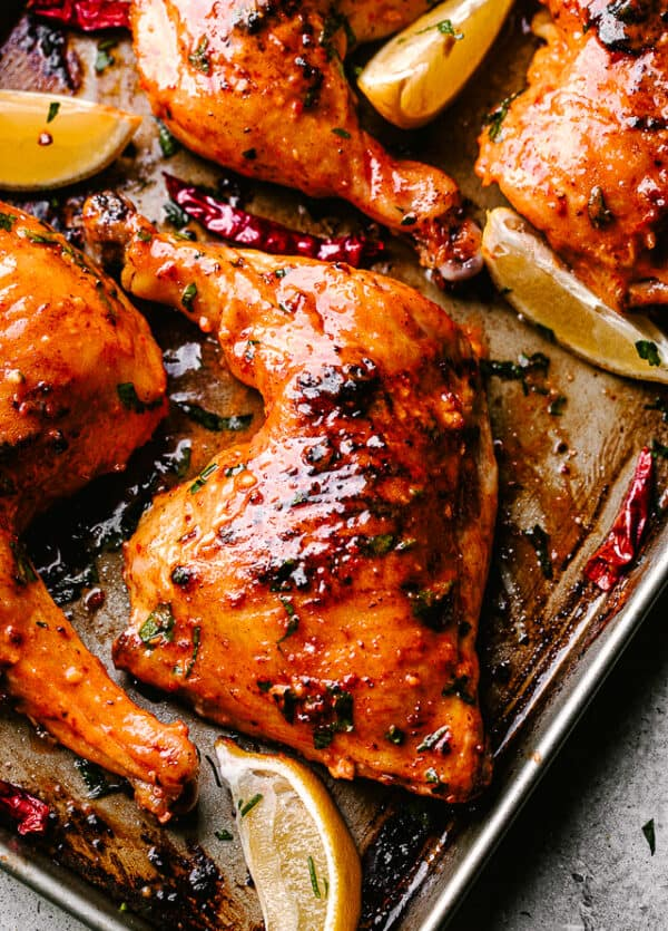 Piri Piri Chicken out of the oven and garnished with lemon wedges.