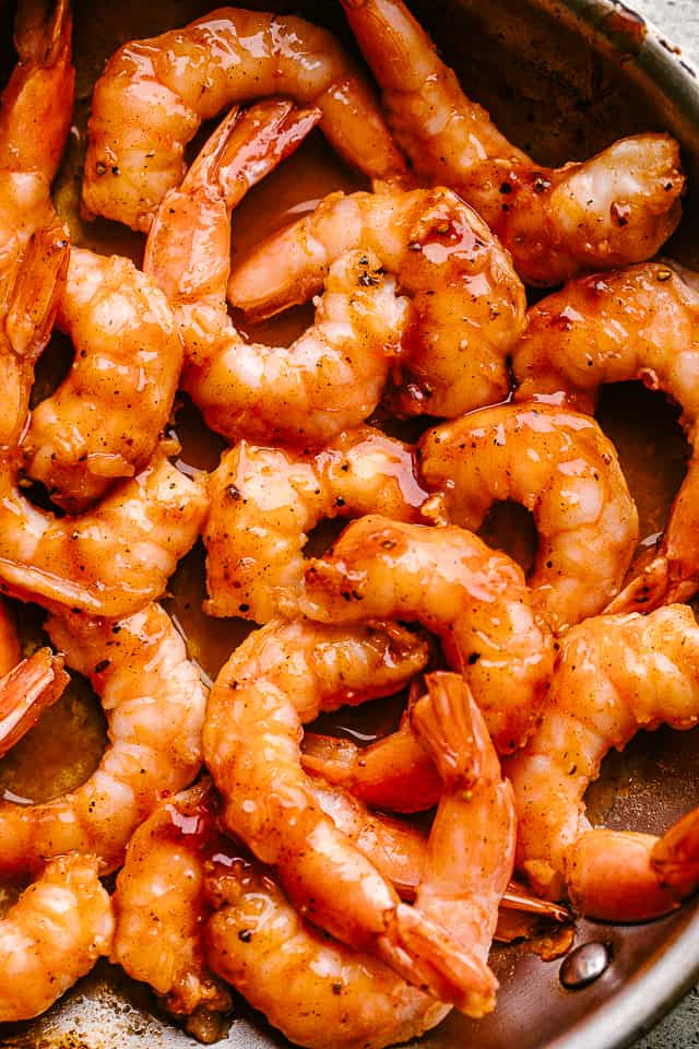 Shrimp simmering in a pan with barbecue sauce