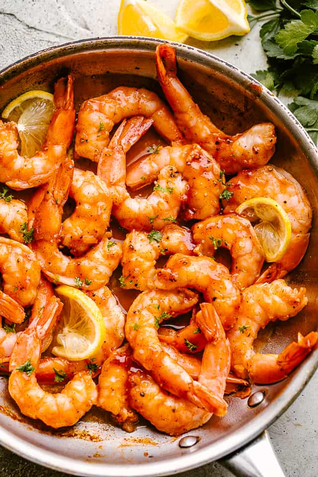 Skillet barbecue shrimp in a pan garnished with lemon wedges and parsley