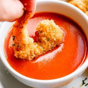 Hand dipping crispy air fried shrimp in buffalo sauce.