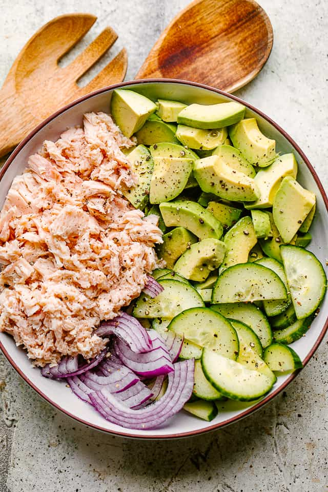 canned tuna, sliced avocados, cucumbers, and onions in a bowl