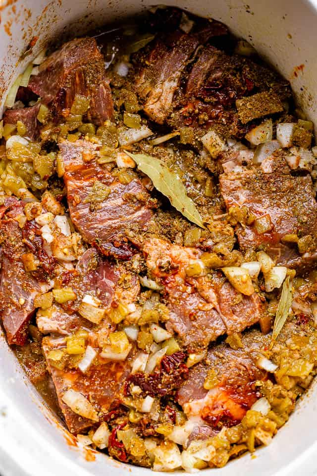 beef in slow cooker with green chilies, onions, and bay leaf