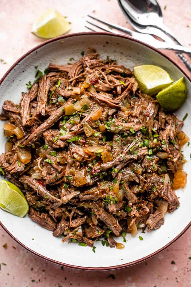 pulled beef barbacoa served in a bowl with lime wedges