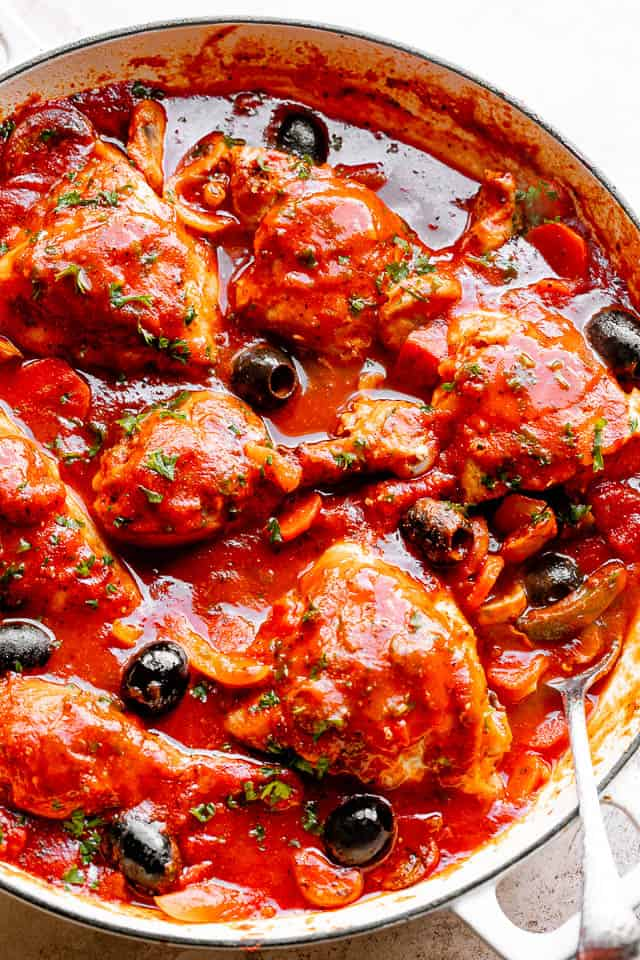 Chicken Cacciatore in a pot with veggies, olive, and fresh herbs.