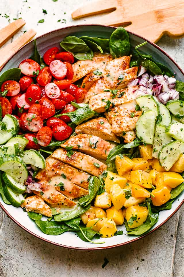 sliced chicken breasts, chopped mangoes, sliced cucumbers, and halved cherry tomatoes set over a bed of lettuce