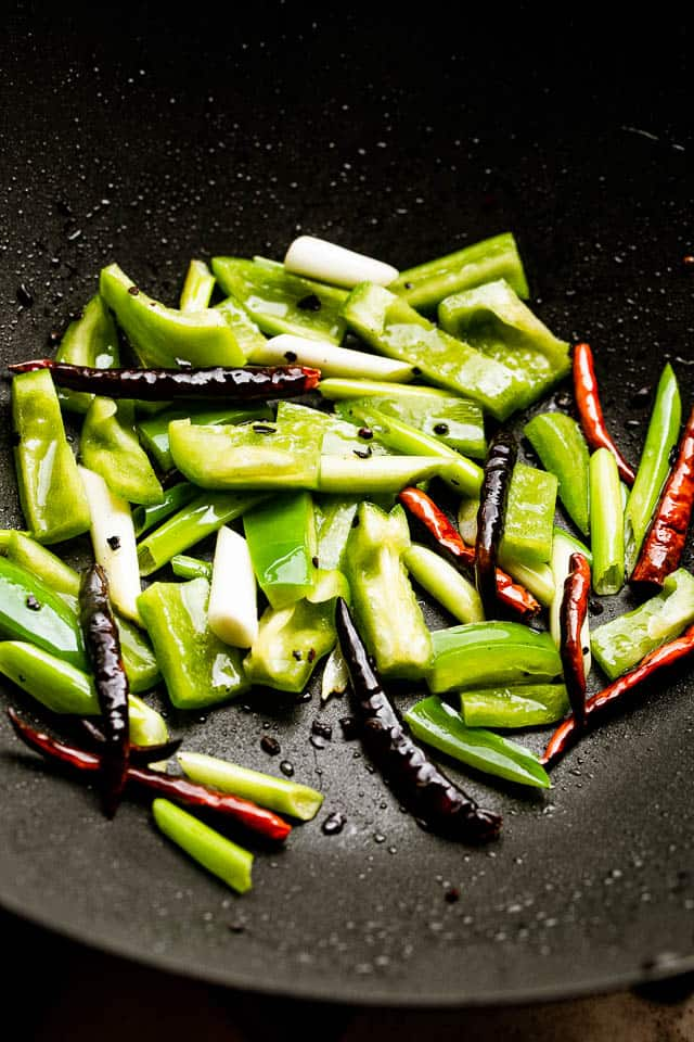 Green bell peppers and Thai chilies sauteing in a wok.