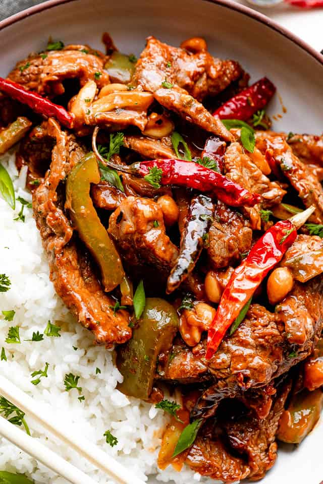 close up shot of Kung Pao beef served on a plate with a side of white rice.