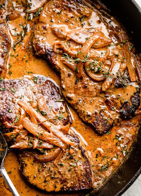 two steaks in a cast iron skillet topped with onion gravy