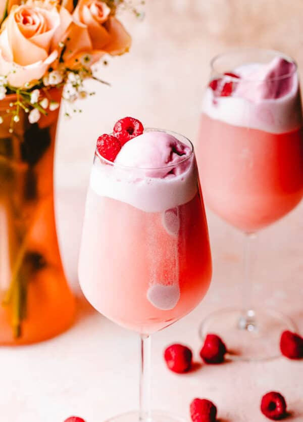 rose floats in wine glasses topped with sorbet and raspberries