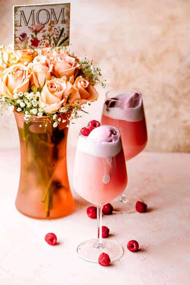 Two glasses of rosé sorbet floats garnished with raspberries next to a vase with Mother's Day flowers.