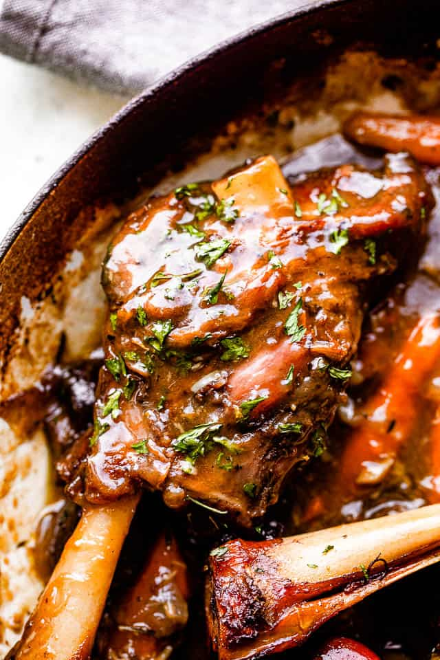 lamb shanks cooking in wine sauce